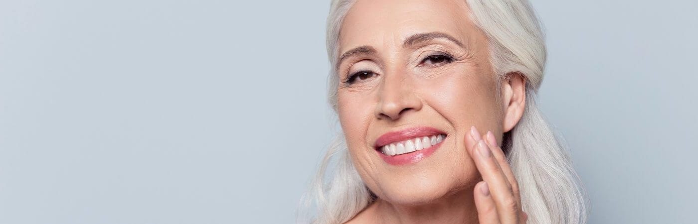 Old Woman with Grey Hair Stroking Face